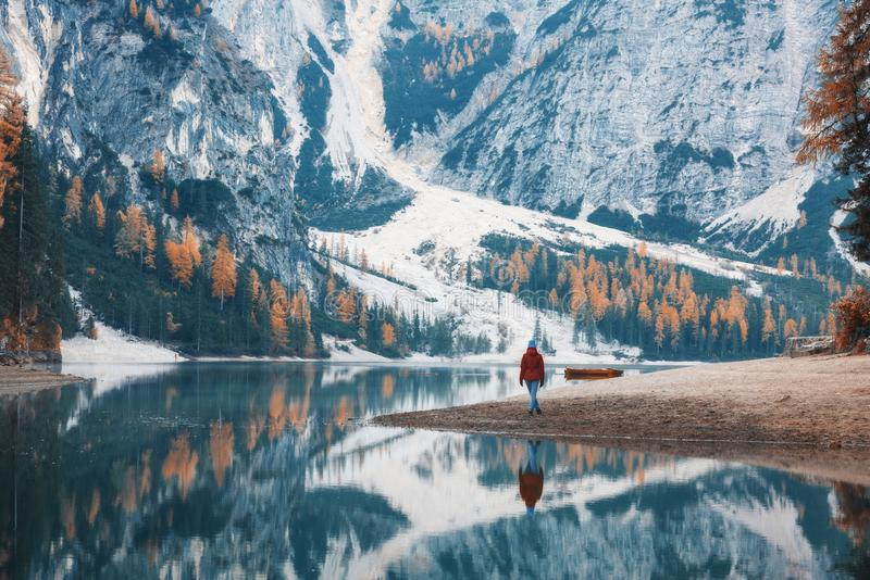 Woman on the coast of Braies lake in the morning in autumn royalty free stock images