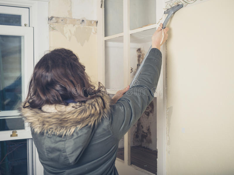 A Young Woman Wearing Warm Winter Coat Is Renovating House And Stripping Off The Wallpaper
