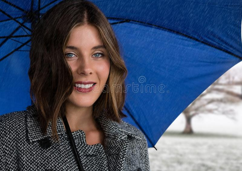 Woman in coat with blue umbrella in snow landscape. Digital composite of Woman in coat with blue umbrella in snow landscape stock photo