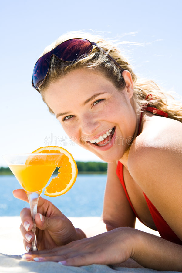 Woman with cocktail. Photo of beautiful woman holding a orange cocktail and laughing royalty free stock images