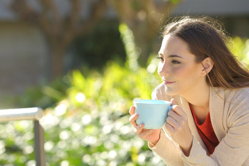 Woman with a coffee cup contemplating at the park. Relaxed woman holding a coffee cup contemplating sitting at the park royalty free stock photography