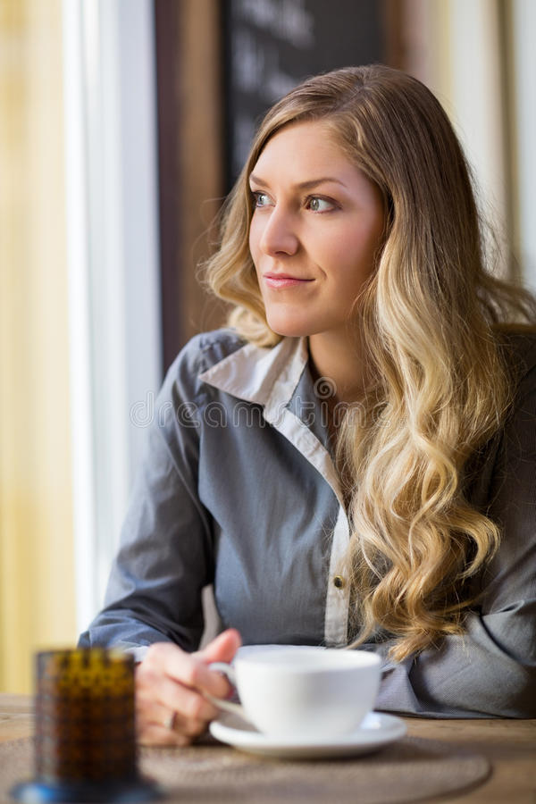 Woman With Coffee Cup Looking Out Window stock images