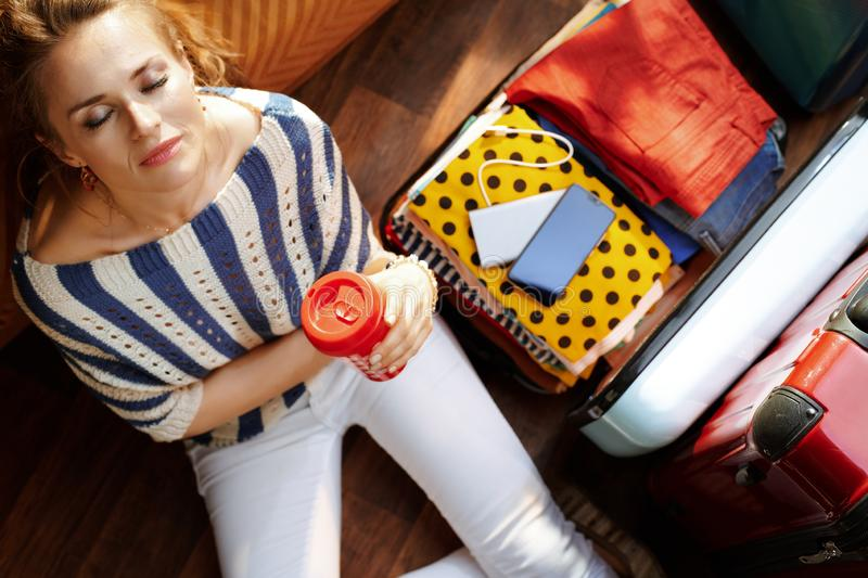 Woman with coffee cup in modern house in sunny summer day. Upper view of relaxed elegant woman in white pants and striped blouse with coffee cup near open travel royalty free stock photo