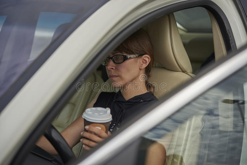 Woman with a coffee while driving car royalty free stock photos
