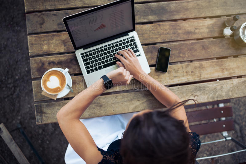 Woman at coffee shop checking time on smartwatch. Overhead view of young woman checking time on her smartwatch while working on her laptop at a cafe. Top view royalty free stock photography