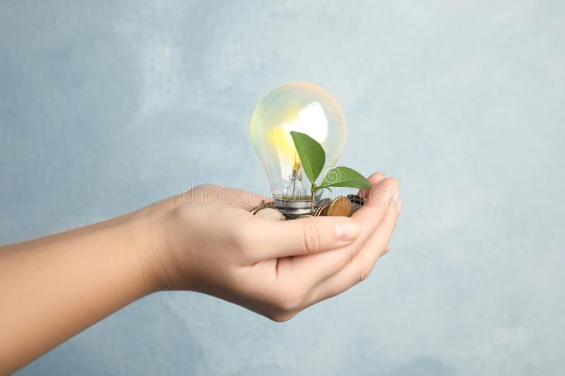 Woman with coins, light bulb and green plant on background, closeup. Power saving stock photo