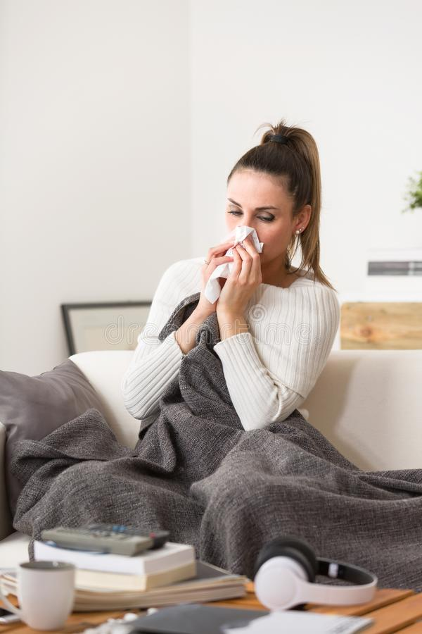 Woman in cold and flu sneezing nose with tissue royalty free stock photography