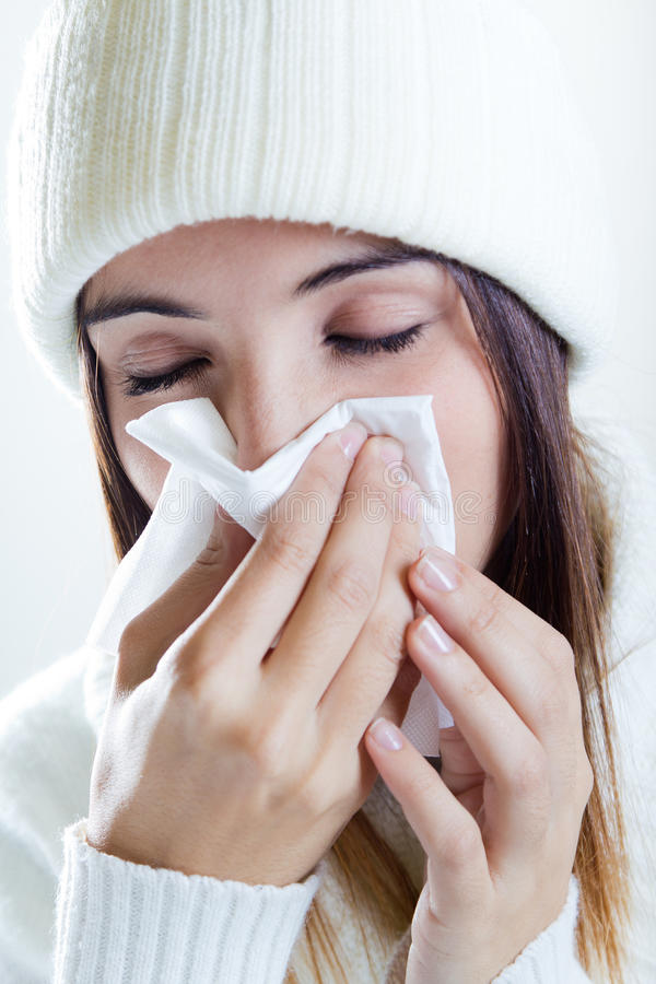 Woman with a cold. Pretty young brunette woman with a cold stock image