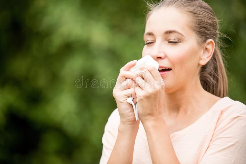 Woman with a cold sneezing. From allergy or hay fever stock photos