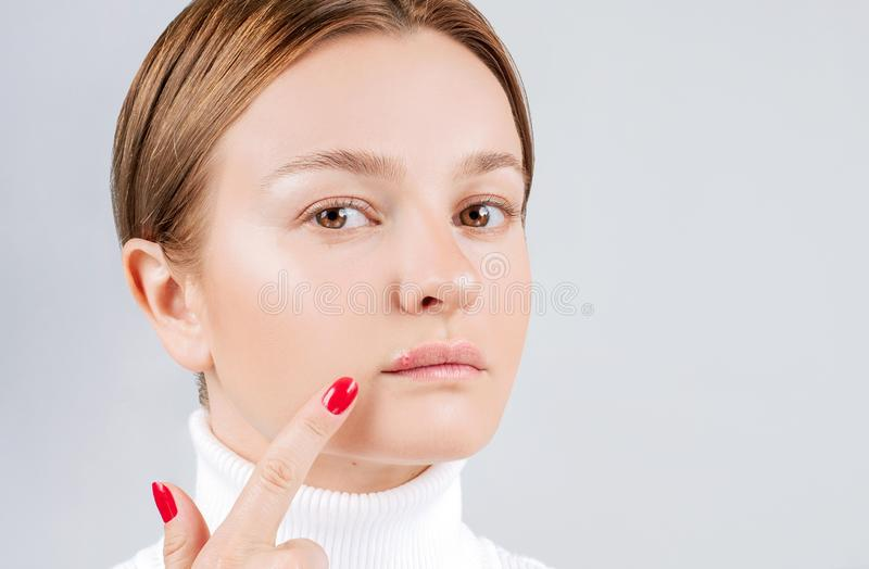 Woman with cold sore touching her lips. Herpes on lips royalty free stock photo