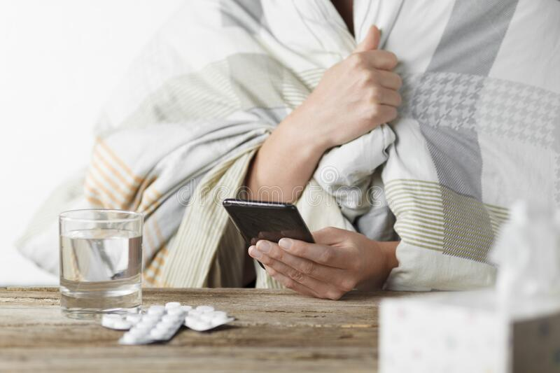 Woman with cold writes symptoms in chat with doctor on smartphone. Remote consultation, telemedicine. Help and diagnosis stock photography