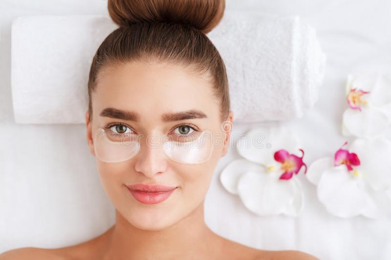 Woman with collagen pads under her eyes in spa salon stock images