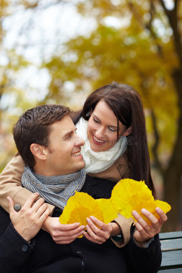 Woman collecting autumn leaves. Women collecting autumn leaves and showing them to men royalty free stock photos
