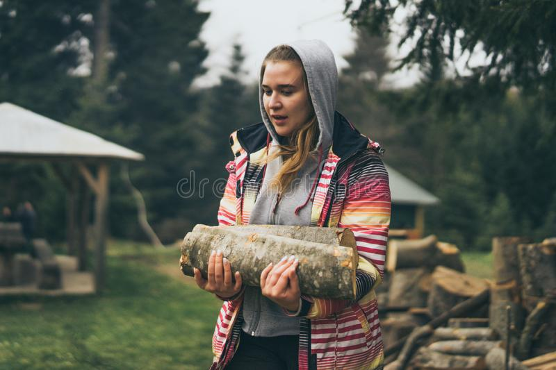 Woman collecting firewood in autumn garden, smiling, side view, portrait royalty free stock images