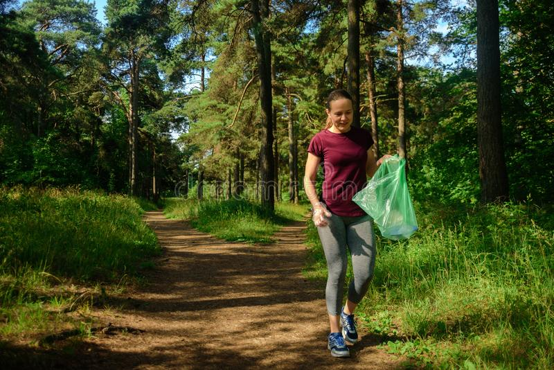Woman collecting garbage in forest royalty free stock photography