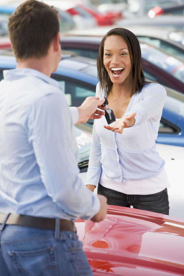 Woman collecting keys to new car stock image