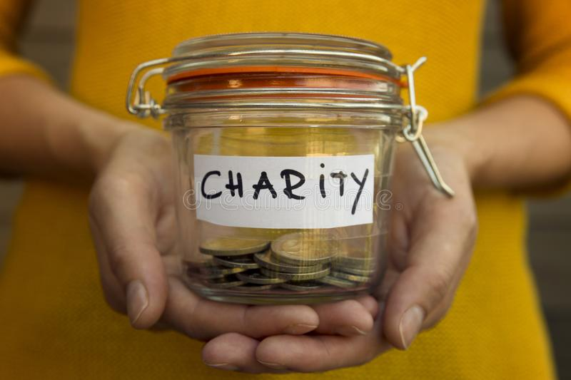 Woman collecting money for charity and holds jar with coins. royalty free stock images
