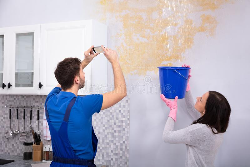 Repairman Taking Photo On Mobilephone Of Water Damage. Woman Collecting Water In Blue Bucket From Damaged Ceiling While Repairman Taking Photograph On stock photo