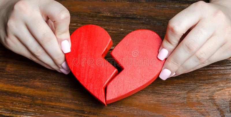 A woman collects a broken heart in his hands. Concept of love and relationships. Family psychotherapist services. Reconciliation. royalty free stock photos