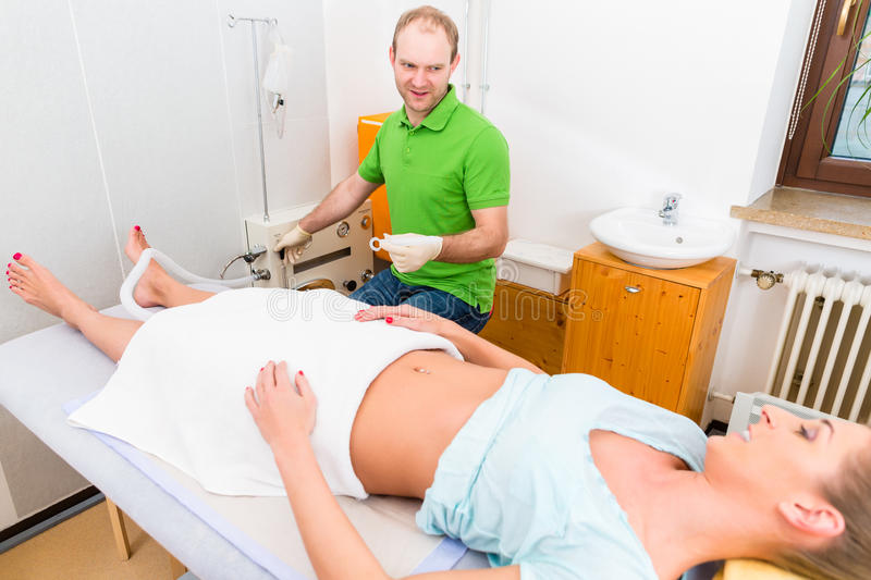 Woman at colon therapy with alternative practitioner royalty free stock photography