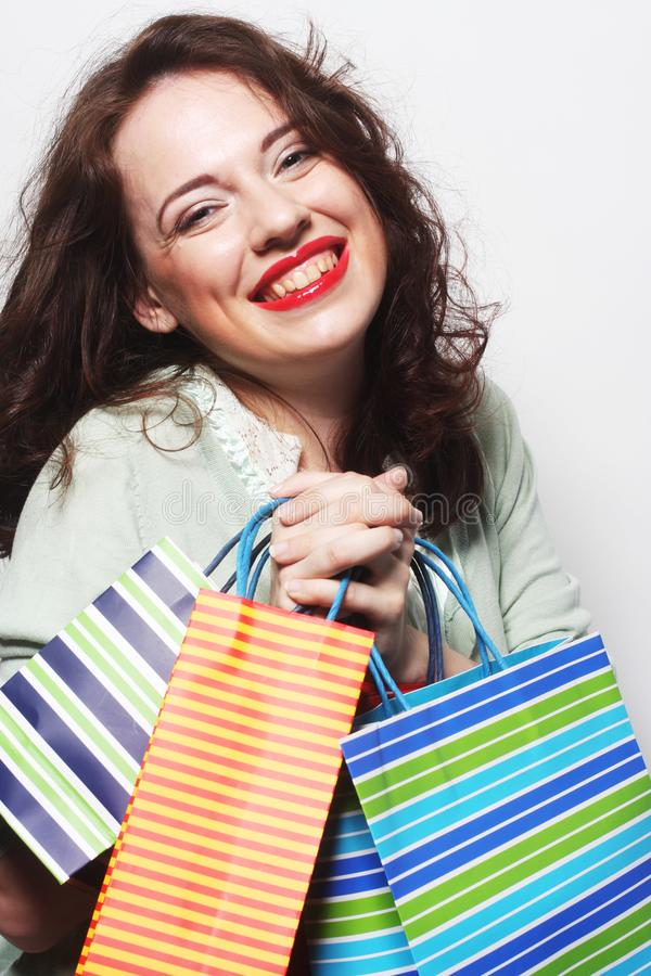 Woman with colored shopping bags. Portrait of a beautiful woman with colored shopping bags stock photography