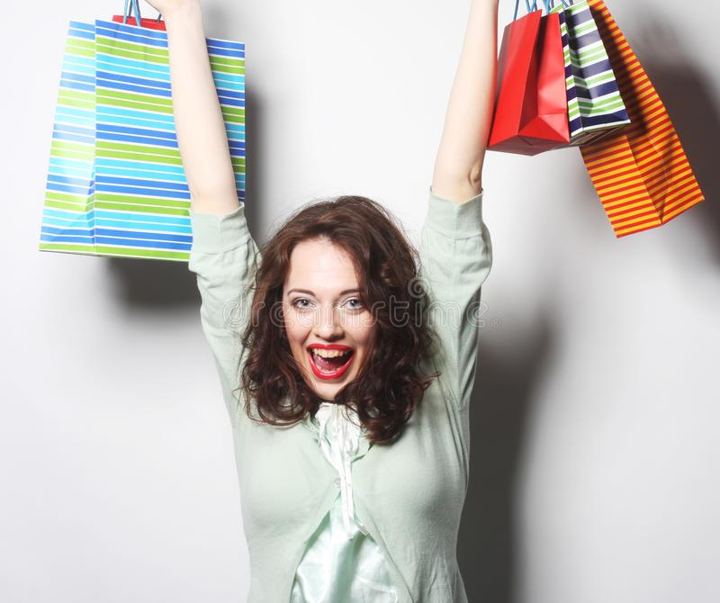 Woman with colored shopping bags. Portrait of a beautiful woman with colored shopping bags stock image