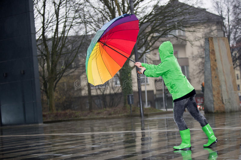 Woman with a colored umbrella fights against a storm stock photography