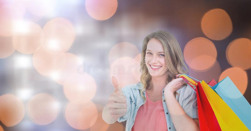 Woman with colorful bags showing thumbs up stock images