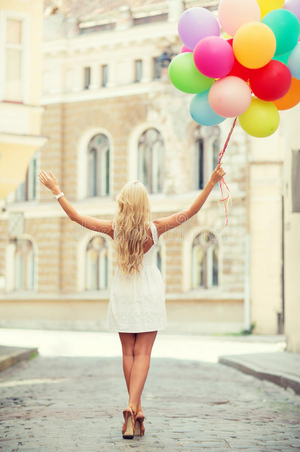 Woman with colorful balloons. Summer holidays, celebration and lifestyle concept - beautiful woman with colorful balloons in the city royalty free stock photography