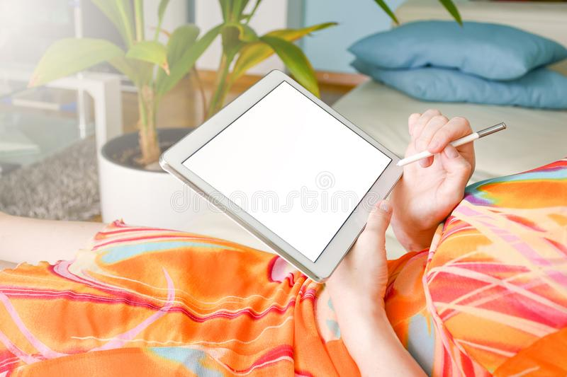 Woman in colorful dress in a living room writing with a pen on a the white tablet stock photos