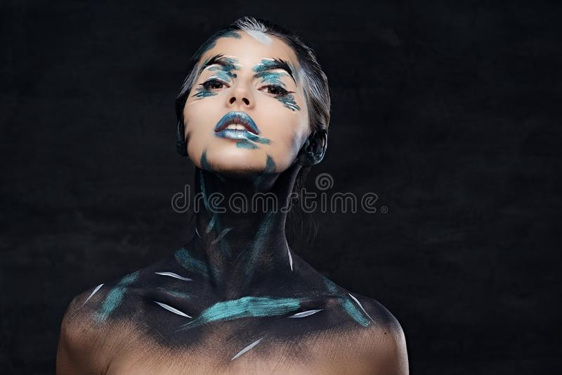 A woman with colorful make up and painted art on a neck. royalty free stock photography