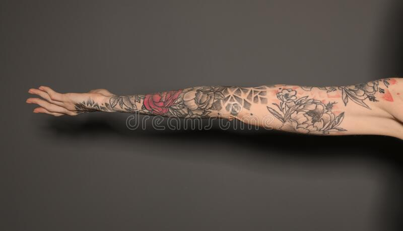 Woman with colorful tattoos on arm against dark background, closeup. Woman with colorful tattoos on arm against dark grey background, closeup stock image