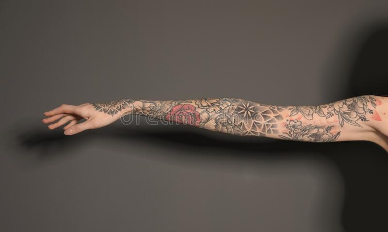 Woman with colorful tattoos on arm against grey background, closeup. Woman with colorful tattoos on arm against dark grey background, closeup stock photos