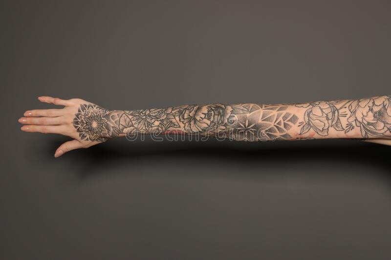 Woman with colorful tattoos on arm against grey background, closeup. Woman with colorful tattoos on arm against dark grey background, closeup stock photography