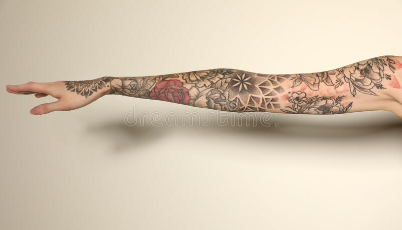 Woman with colorful tattoos on arm against background, closeup. Woman with colorful tattoos on arm against white background, closeup royalty free stock photography