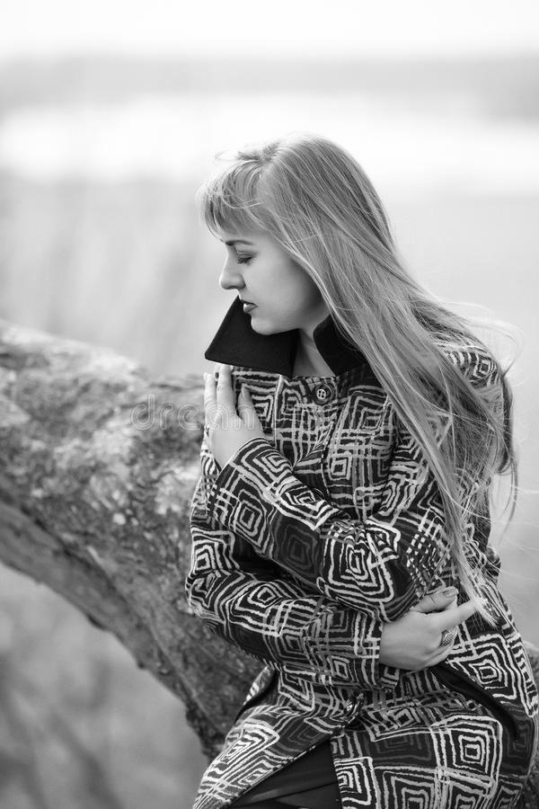 A woman in a coloured coat with sadness, and suffering with a headache on the beach. Outdoor Sad Woman royalty free stock photography