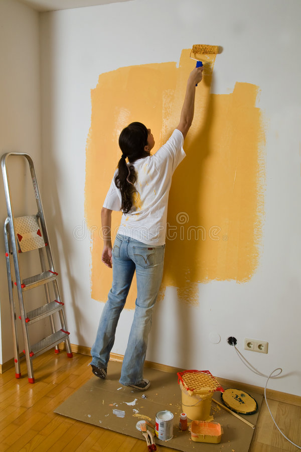 Woman colours her apartment stock images