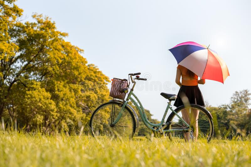 Woman with colrful umbrella and bicycle in park. People and relaxation concept. Season and Autumn theme royalty free stock image