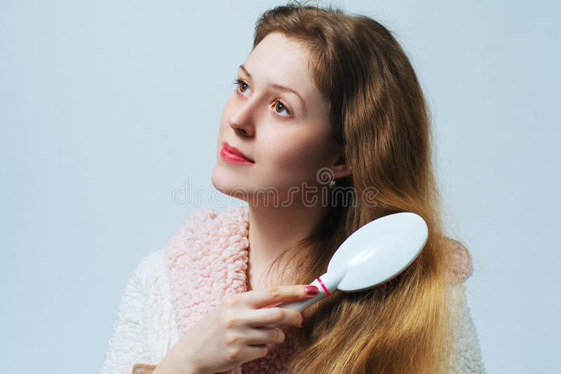 Woman comb hair. Young blond woman in bathrobe comb hair after washing. On white background royalty free stock photo