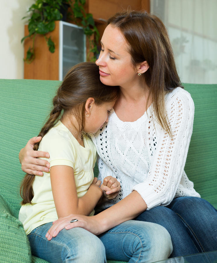 Woman comforting crying little daughter stock photo
