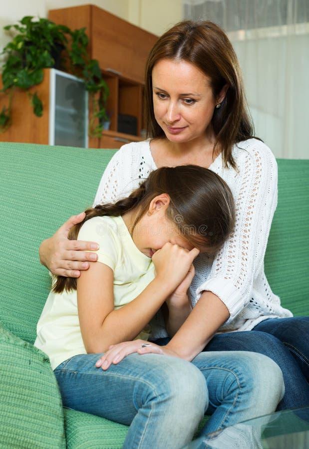 Woman comforting sad crying daughter stock image