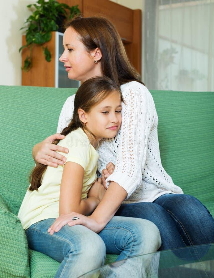 Woman comforting sad little daughter stock image
