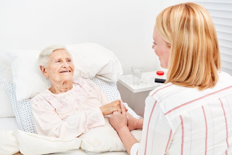 Woman comforts bedridden elderly woman as a patient stock images