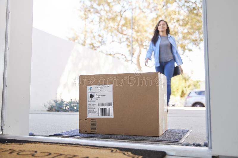 Woman Coming Back To Home Delivery In Cardboard Box Outside Front Door stock images