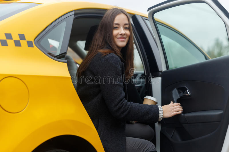 Woman coming out of cab. Pretty woman with coffee in hand coming out of cab royalty free stock images
