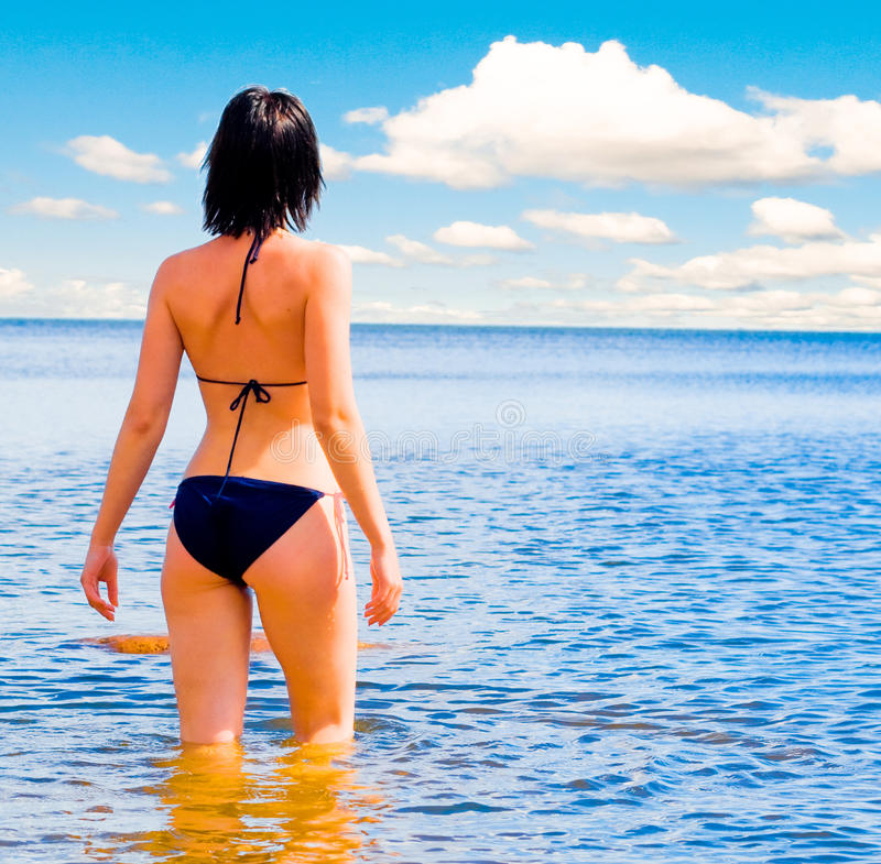Woman coming into sea royalty free stock photography