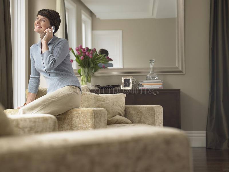 Woman Communicating On Cell Phone. Happy woman communicating on cell phone in house royalty free stock photo