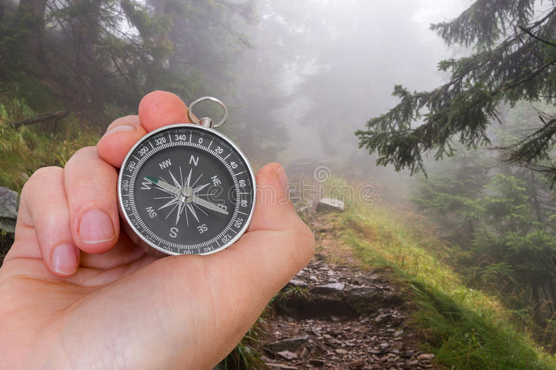 Woman with compass is seeking a right way in forest. Navigation concept stock images