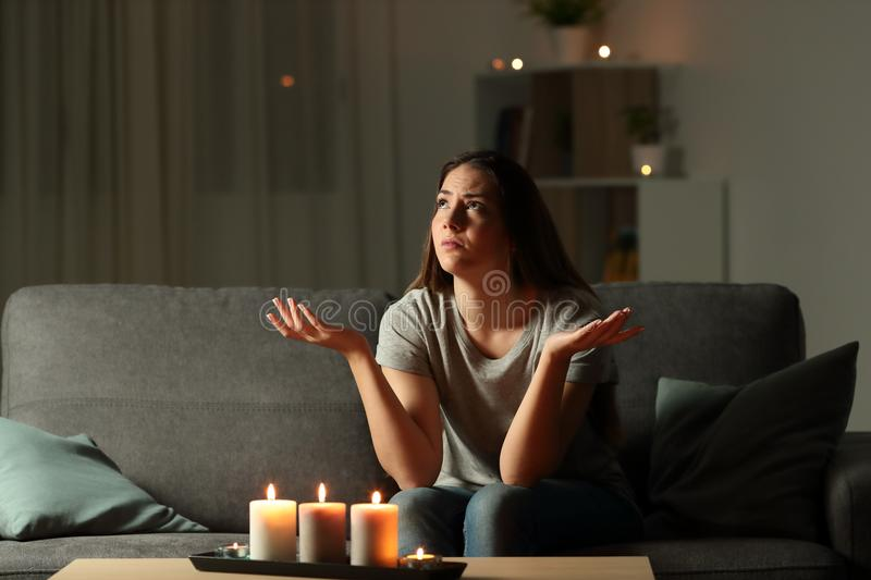 Woman complaining during a blackout at home. Woman complaining during a blackout sitting on a couch in the living room at home royalty free stock image