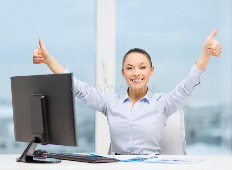Woman with computer, papers showing thumbs up stock image
